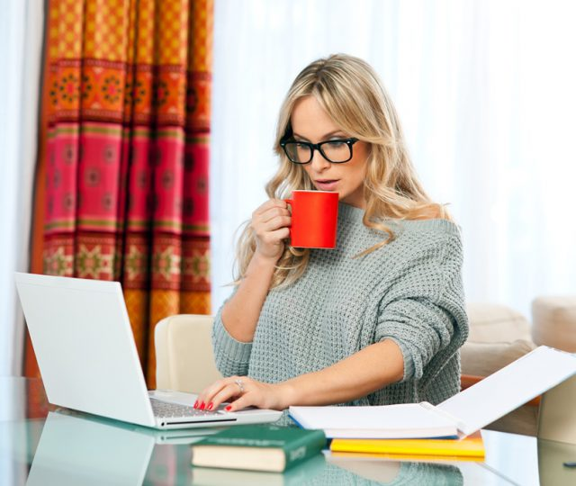 woman-with-cup-of-coffee-book-and-laptop-sitting-at-her-home-desk-and-working